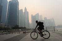 Singapur, Republik Singapur, Radfahrer faehrt durch das Smog verschleierte Geschaeftsviertel in Marina Bay