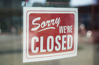 Sorry we're closed sign behind dirty glass door