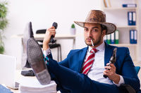Young businessman cowboy working in the office