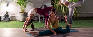 Asian weman group do yoga in city at night panorama