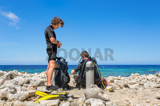 Two divers on the beach prepare for diving