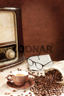 A cup of coffee with newspaper and radio