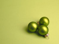 Green vintage Christmas baubles on a green background