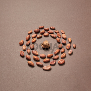 Cacao peas in the shape of round frame with cocoa mass.