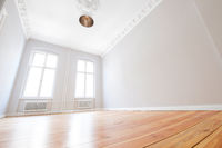 empty apartment room with wooden floor after renovation in beautiful old building