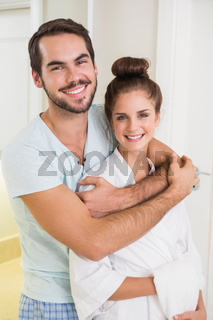 Young couple hugging and smiling at camera