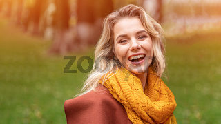 Joyful young woman in autumn coat and yellow knitted scarf standing joyful smiling in the fall yellow garden or park. Beautiful smiling young woman in autumn leaves
