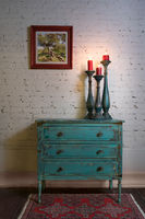 Green vintage cabinet, candlesticks and hanged painting on bricks wall