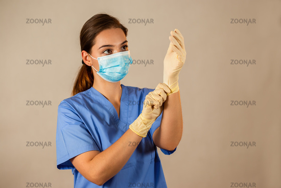 Adult woman looking at her hands with rubber gloves