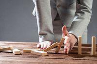 Business woman hand block domino effect