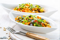 Mixed salad of roasted vegetables with arugula and  seeds on wooden background