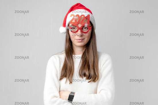 Caucasian young beautiful woman with red santa hat and 2021 glasses. Christmas new year