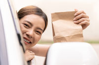 Asian woman holding food bag from drive thru service restaurant