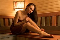 Sexy naked woman in sauna full-length view