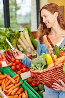 Frau kauft Gemüse mit Einkaufsliste im Biomarkt