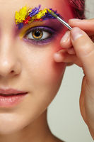 Artist's hand with paintbrush painting beautiful girl's brows make-up.
