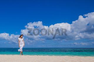 Woman in dress walking on beach