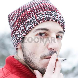 Mann raucht eine Zigarette im Winter