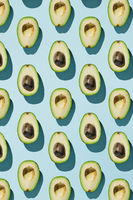 Vertical pattern of cut avocado on blue background, healthy eating concept