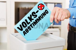 Hand mit Stimmzettel bei Volksabstimmung
