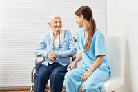 Alte Seniorin im Rollstuhl mit Frau vom Pflegedienst