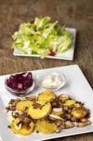 bayerisches Gröstl mit Salat auf Holz