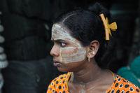 Yangon, Myanmar, Portrait einer jungen Frau mit Thanakapaste Make-up im Gesicht