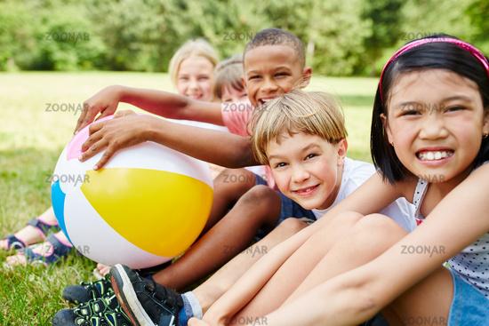 Multikulturelle Gruppe Kinder mit Ball im Sommer