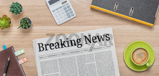 A newspaper on a desk with the headline Breaking News