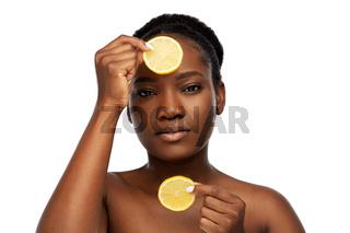 african woman making eye mask of lemons