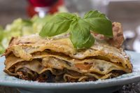 Lasagne mit Salat auf dunklem Holz