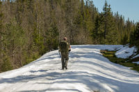Man with big backpadk walks along the snow covered road in spring
