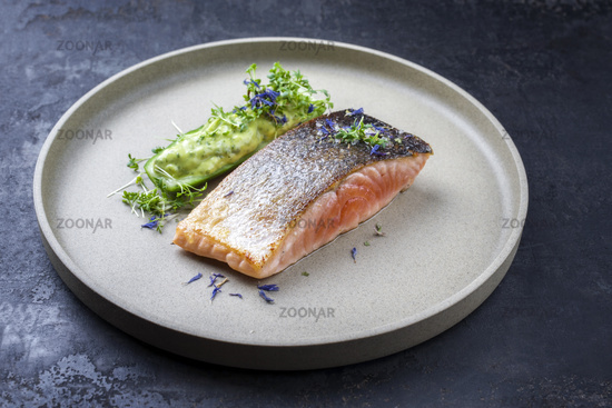 Minimalistic design salmon fish filet glazed with avocado and wasabi creme in a sliced cucumber as closeup on a modern design plate decorated with herbs