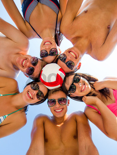 smiling friends in circle on summer beach