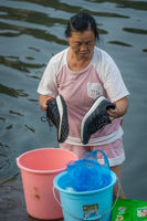 Chinese woman washing shoes in the river