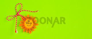 Bulgarian Martenitsa and sun on green background