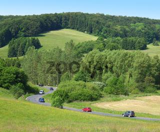 Landstraße mit Autos in idyllischer Landschaft