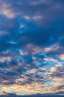 Beautiful clouds in blue sky, illuminated by rays of sun at colorful sunset to change weather