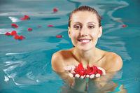 Frau mit Blütenblättern von Rosen im Wasser
