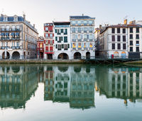 Old building facades reflecting in the Nive River in Bayonne, France