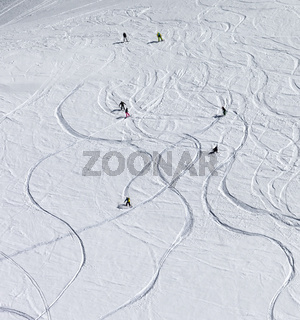 Snowboarders and skiers descend on snowy off-piste slope