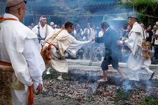 Monks helping men with fire walk ceremony at Honsen-ji temple during Shinagawa Shukuba Matsuri Festival in Tokyo, Japan