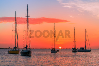 Group of sailing boats on sea at sunset