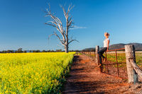 Country woman basking in the spring sunshine looking out over the fields of canola