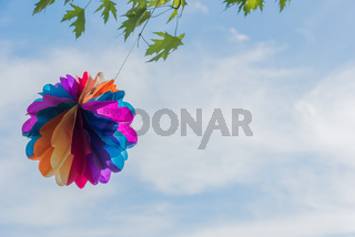 A paper balloon hangs on a branch against a blue sky