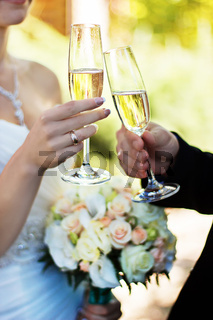 Bride and groom clinking glasses on wedding-day.