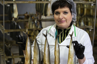 September 18, 2020. Belarus, Gamil. Fish factory.Fish factory worker holds smoked fish.