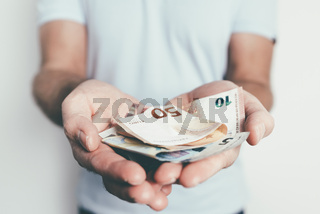 caucasian man offering or handing over money to someone else