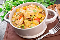 Chicken with vegetables and peas in saucepan on board