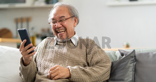 Panorama Elderly man use cellphone to make video call to his family